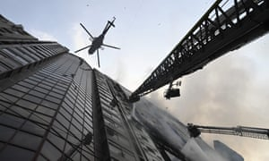 A helicopter carries water to drop on the burning office building.