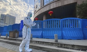 A worker in protective overalls and carrying disinfecting equipment walks outside the Wuhan Central Hospital.