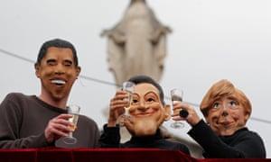 Anti G20 demonstrators wearing masks of US President Obama, Germany's Chancellor Merkel and France's President Sarkozy in 2011.