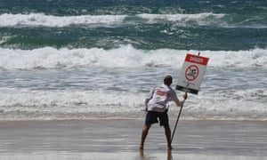 A lifeguard places a danger sign on the Gold Coast as Cyclone Oma brings hazardous surf conditions and abnormally high tides