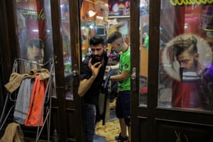 A man talks to a customer as he stands inside his barber shop in the Old City.