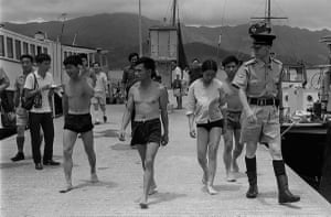 Four 'freedom swimmers' from China are led away by Hong Kong police for questioning at Tai Po Kau on May 31, 1971.