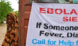 A woman stands beside a banner conveying Ebola advice in Kailahun, one of the Sierra Leonean districts worst hit by the outbreak.