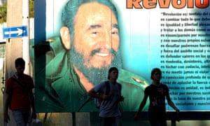Pedestrians pass by a poster of Cuban leader Fidel Castro, in Havana.