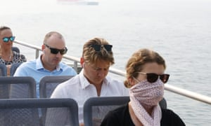 A woman wears a face mask while travelling on a Sydney ferry as smoke haze shrouds the harbour. Children, the elderly and those with heart and lung conditions are most at risk from poor air quality caused by bushfires burning across NSW and southern Queensland.