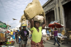 Women balance goods on their heads as they make their way through the Croix-des-Bossales market