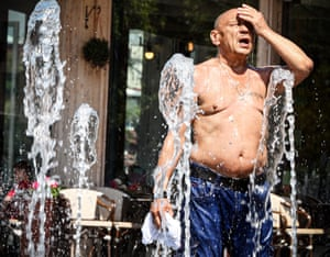 A man splashes his face as he tries to cool himself in a fountain
