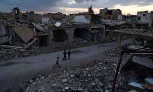 Syrian children walk past heavily damaged buildings in the rebel-held town of Douma
