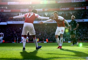 Alex Iwobi celebrates with Mesut Ozil after scoring Arsenal's third goal.