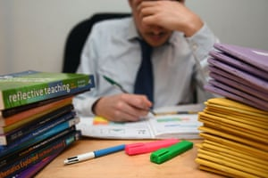 Teacher next to a pile of classroom books
