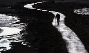 A man walks along a pathway on the shores in Strangford Lough, Northern Ireland