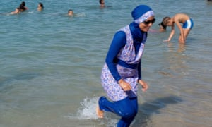 A woman wearing a burkini paddles in Marseille