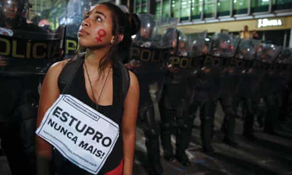 A protester standing before a police barricade, her face painted with the female gender symbol, bears a sign reading: 'Rape never more'