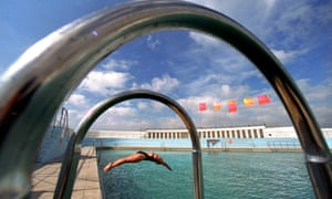 A swimmer dives into the Penzance Lido, Cornwall, UK