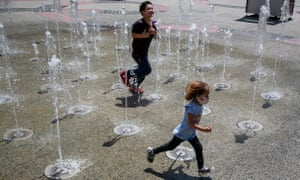 Kids run through water spouts as they cool off in Los Angeles, California, as the state sees extreme temperatures.