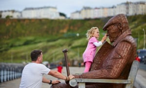 A girl plays on a statue on Scarborough seafront