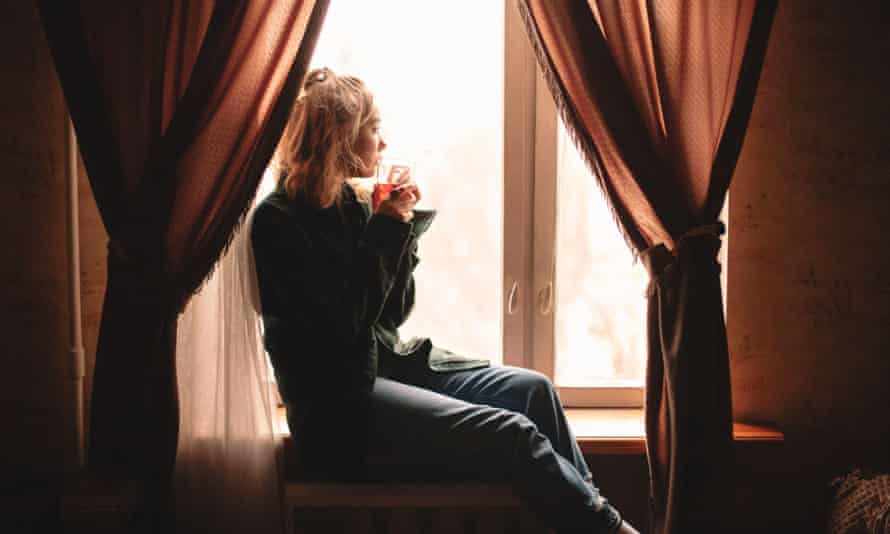 Young thoughtful woman drinking tea and looking through window while sitting on windowsill at home2B99TD5 Young thoughtful woman drinking tea and looking through window while sitting on windowsill at home