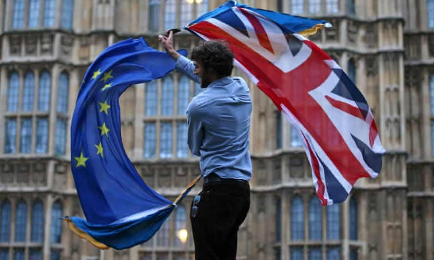 A man waves a union flag and an EU flag together outside the Houses of Parliament