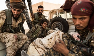 SDF fighters who got injured while trying to assist a cut-off team of their unit, seen on the back of truck while being transported in a near-by field hospital.