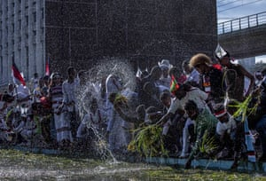 Ethiopians throw grass into a pool of water at the annual Irrecha thanksgiving festival in Addis Ababa