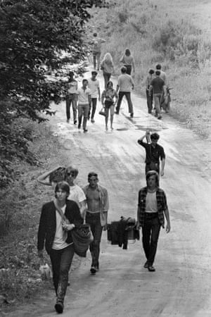A group of people walk down the road at the Woodstock Music Festival, Bethel, NY, August 15, 1969.