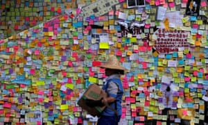 A worker walks past post-it notes scribbled with messages, left behind by protesters on the walls of the Legislative Council.