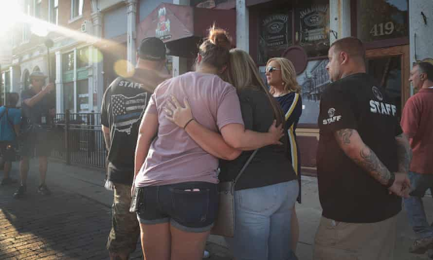 Workers and patrons gather before the start of a memorial service to recognize the victims of a mass shooting in Dayton, Ohio.