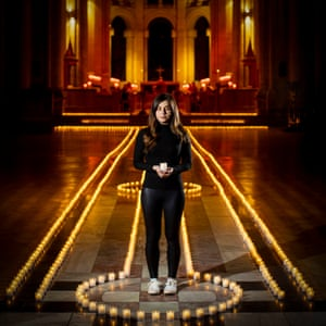 Holly Wilson, whose grandmother Ada Wilson passed away during the pandemic, stands in Belfast Cathedral among 2,100 tea-lights - one for each life lost to Covid in Northern Ireland.