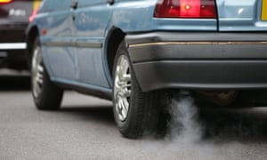 A car emits fumes from its exhaust as it waits in traffic in central London.