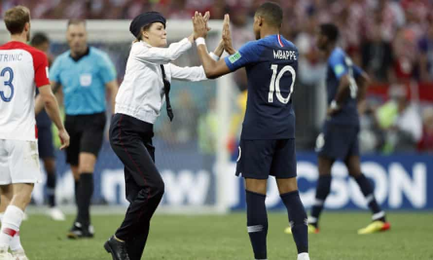 Kylian Mbappe of France high-fives a member of Pussy Riot  during the World Cup final.