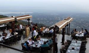 People eat at a rooftop restaurant on Margalla Hills after the government lifted most of the country's remaining coronavirus restrictions, in Islamabad.