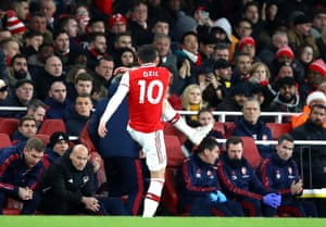 Mesut Ozil of Arsenal kicks a water bottle as he is subbed.