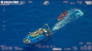 A screengrab taken from an undated video from Frontex shows a fishing trawler pulling away from a wooden boat with refugees and migrants onboard