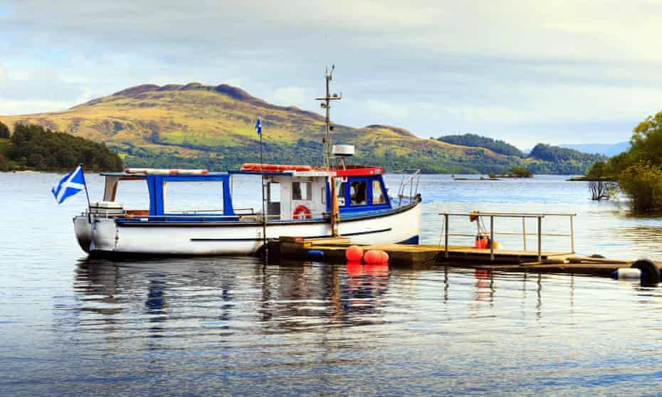 A small passenger ferry at a pier on Loch Lomond.