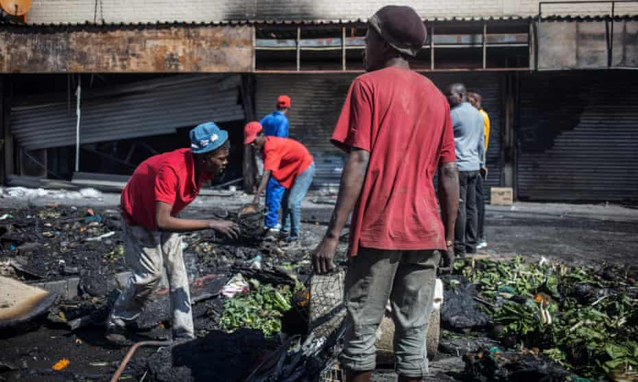 People rummage through items from looted foreign-owned shops in Alexandra township in Johannesburg