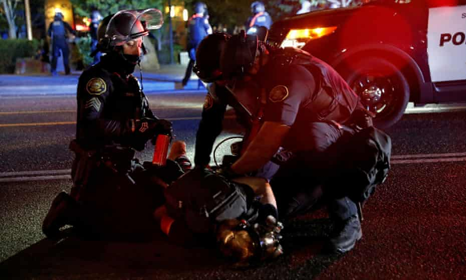 Police officers detain a demonstrator during a protest against police violence and racial injustice in Portland, Oregon, on 24 August.