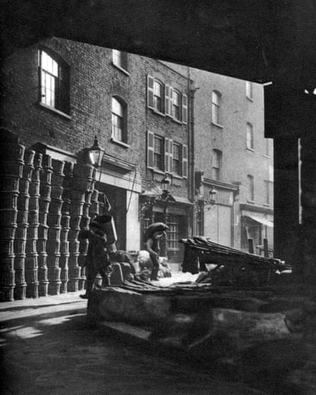 Fruit baskets piled against houses at borough market in the 1920s