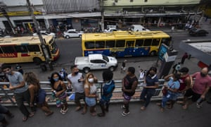 People line up to get a Covid-19 vaccine shot at a train station during a vaccine campaign for people over age 20 in Duque de Caxias, Brazil.