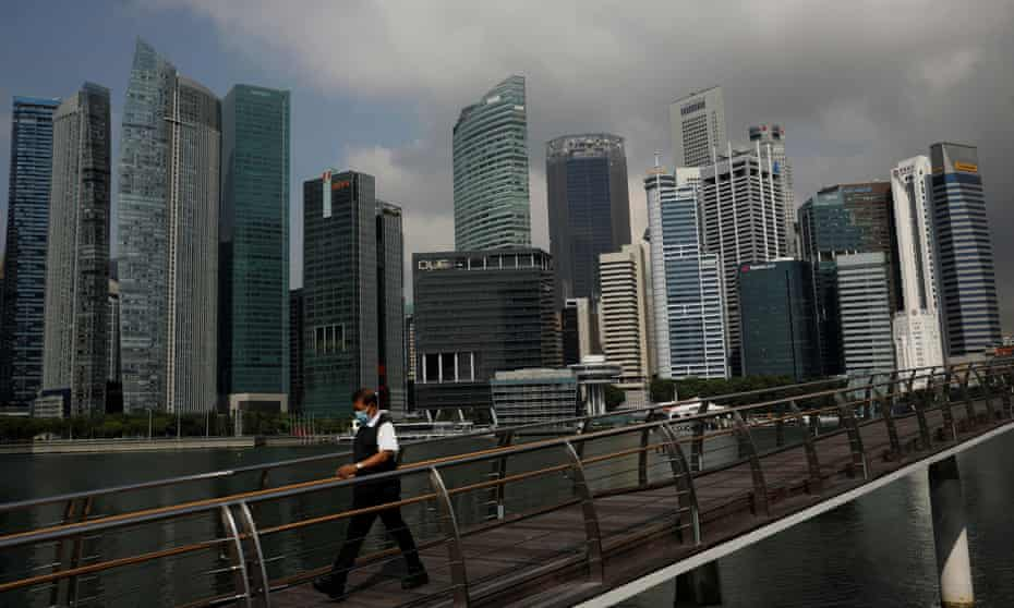A man passes the city skyline during the coronavirus disease outbreak, in Singapore