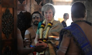 Theresa May stands amidst Hindu priests after offering prayers to the Hindu deity Lord Shiva during a visit to Someshwara Temple in Bangalore.