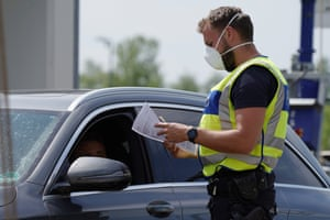 A German border police officers checks the documentation of a driver at a checkpoint at the German-French border.