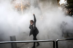 A university student protects herself from teargas while protesting at the University of Tehran.