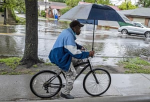 A man rides a bicycle as rain from Tropical Storm Bertha flooded streets in Charleston, South Carolina on 27 May 2020.
