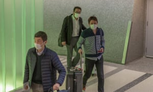 Travelers arrive to the Los Angeles airport wearing medical masks for protection against the coronavirus outbreak on 2 February 2020.