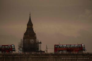 London landmarks including Waterloo Bridge, Big Ben and red buses are transformed by the sepia sky.