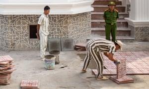 A prisoner lays tiles outside Tu Duc prison.