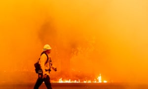 A Pacific Gas and Electric firefighter walks down a road as flames approach in Fairfield, California.