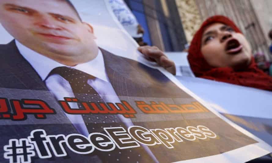 Protesters hold a poster of Egyptian journalist, Mahmoud Moustafa, arrested by police four months ago.