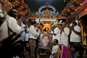 Mumbai, India Well-wishers of Tamil Nadu Chief Minister Jayalalithaa Jayaraman hold her portrait as they pray at a temple