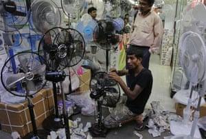 Staff assemble fans at a shop in Kolkata